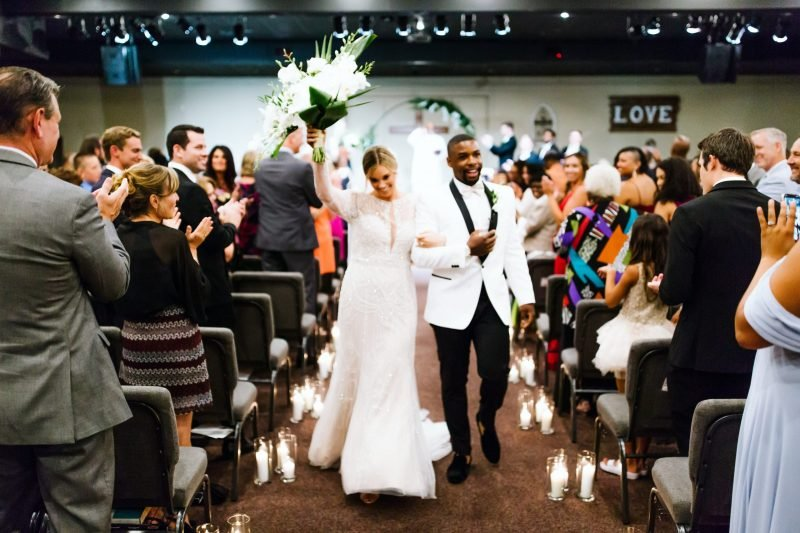 real bride wearing long sleeve wedding dress and groom wearing white tuxedo jacket in church after getting married.